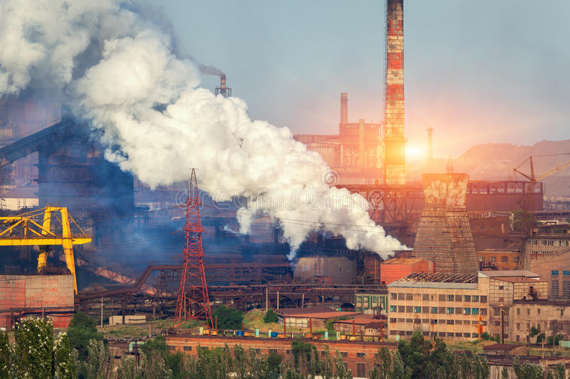 Metallurgy plant in Ukraine at sunset. Steel factory with smog. Pipes with smoke. Steel mill. Heavy industry factory. Metallurgical plant in city. Steel works stock image