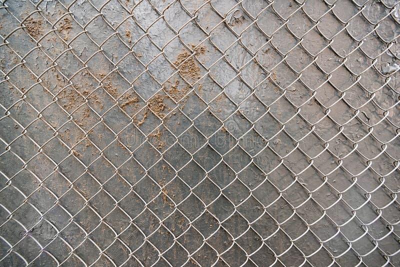 Metallvägg med sand och ingreppsstaketet arkivfoto