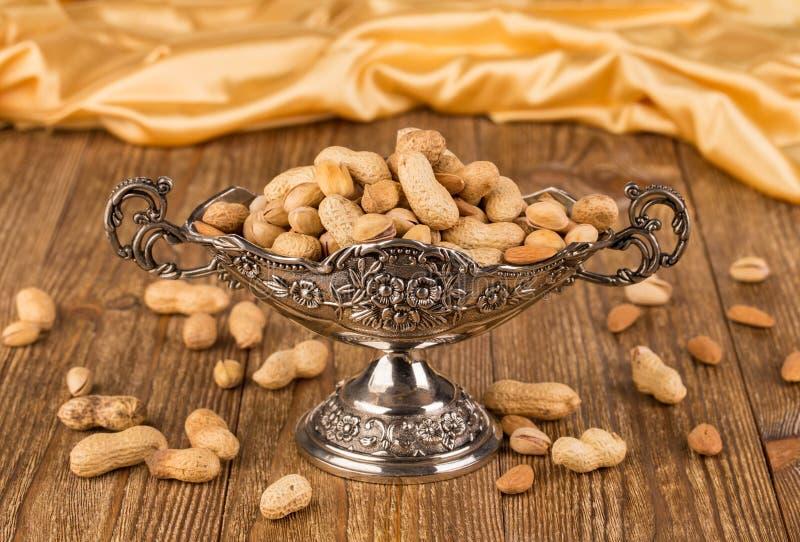 Metallvase mit Erdnüssen stockfotografie