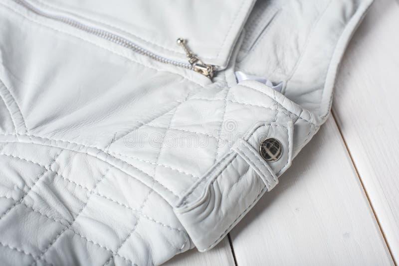 Metallverschlussknopf auf weißer Lederjacke lizenzfreie stockbilder