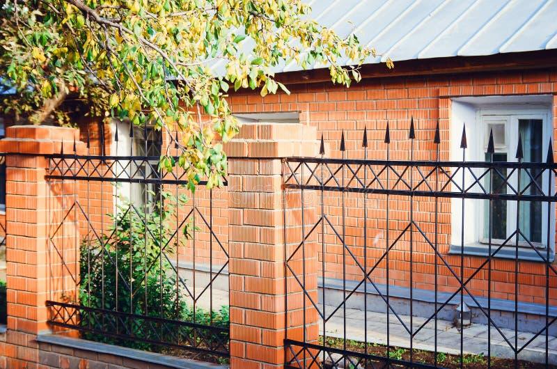 Metallzaun mit Ziegelsteinspalten Ein Landhaus gemacht vom roten Backstein lizenzfreies stockbild
