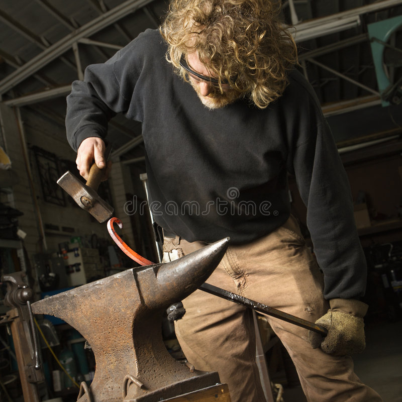 Metalsmith shaping metal. Metalsmith shaping metal on anvil stock photography