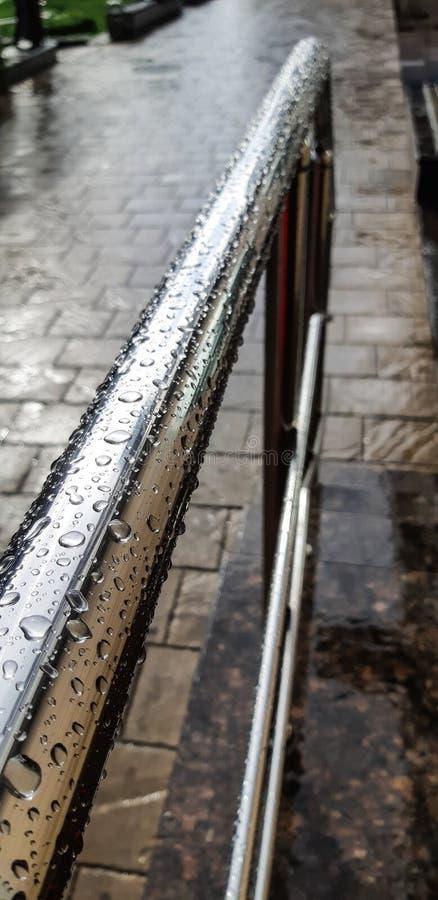 Metalu chrom matrycował poręcz w kroplach deszcz na brukowa chodniczku zdjęcie stock