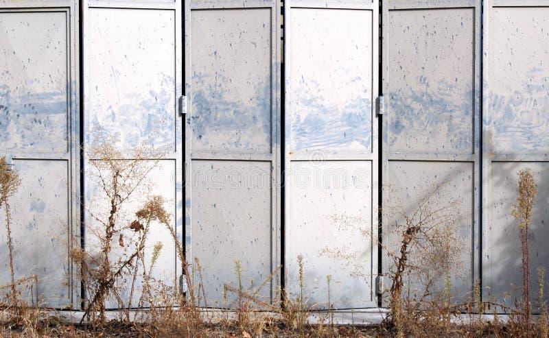 Metalu falcowania szary drzwi na zaniechanym magazynie fotografia stock
