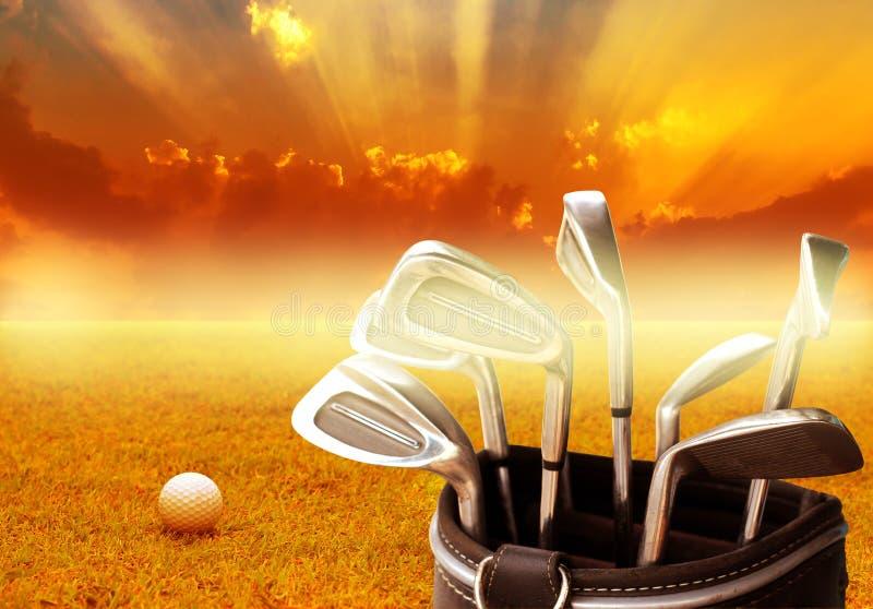 Metalu kij golfowy ustawiający w rzemiennej torbie i piłce golfowej na wschodu słońca tle fotografia stock