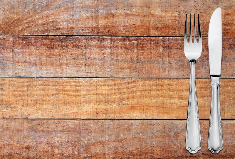 Metalu nóż na drewnianej desce i rozwidlenie zgłaszamy tekstury tło obrazy royalty free
