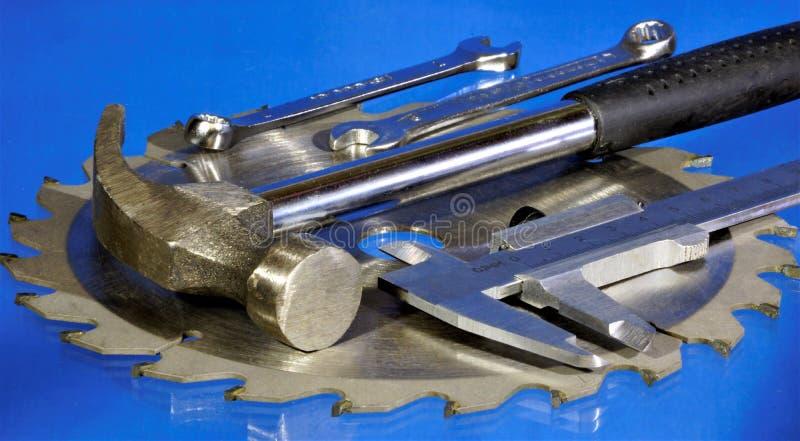 Metalu narzędzie na błękitnym tle, ojca dnia wakacje Popularny locksmith narzędzie dla twórczości stal - młot, zobaczyć ostrze, w zdjęcie stock