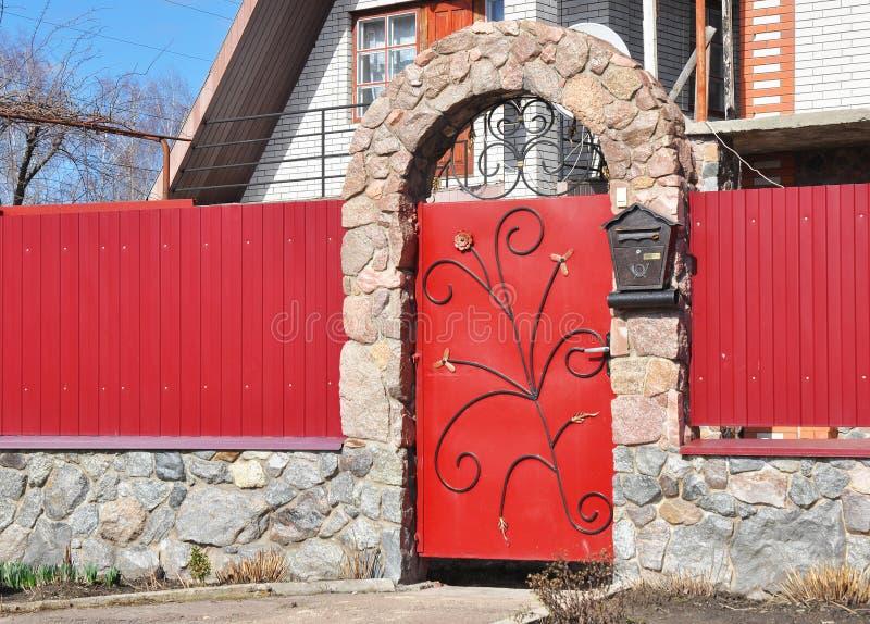 Metalu Płotowy drzwi z czerwonym dzikim kamieniem Metal szermiercza powierzchowność z drzwiowym dzwonem i postbox obraz stock
