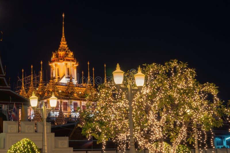 Metalu pałac iluminujący przy nocą z latarniami ulicznymi i drzewem na przedpolu zdjęcia royalty free