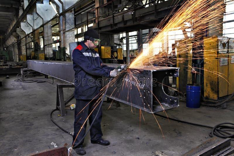 Metalu pracownika zgrzytnięcia spawają stalowe sekcje używać kąta ostrzarza zdjęcia stock