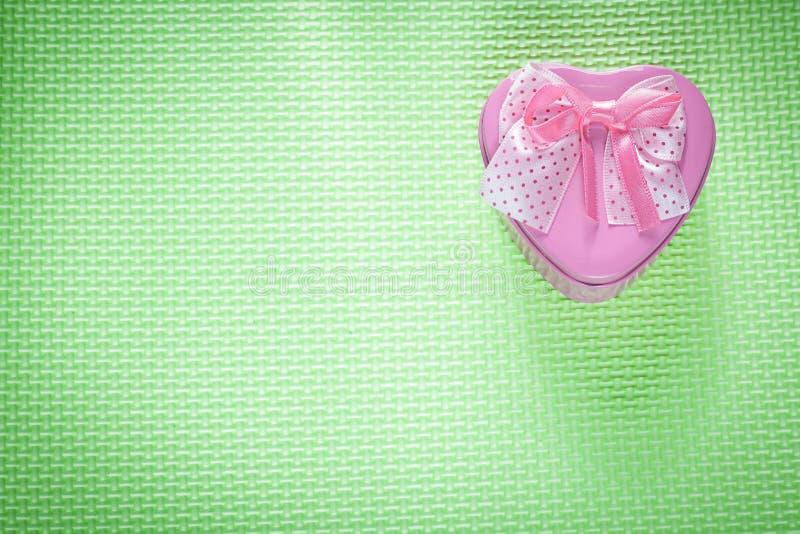 Metalu prezenta różowy sercowaty pudełko z faborkiem na zieleni powierzchni ho fotografia royalty free