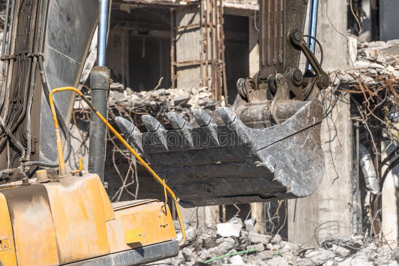 Metalu wiadra ekskawatoru hydrauliczny huk kopie kamienie i gruzy wyburzający budynek Zamyka w górę widok obraz stock