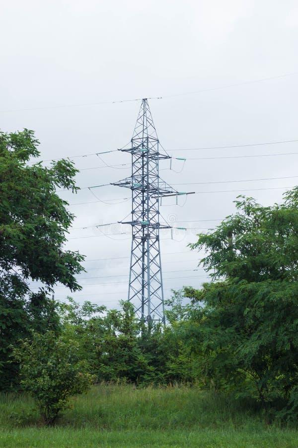 Metalu wysokonapięciowy poparcie, elektryczna wiertnica przeciw niebu, las zdjęcie royalty free