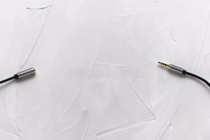 Metalu złota prymka na czarnym audio instrumentu kablu na gipsującym tle w górę od prawej do lewej, Mieszkanie nieatutowy kosmos  obrazy stock