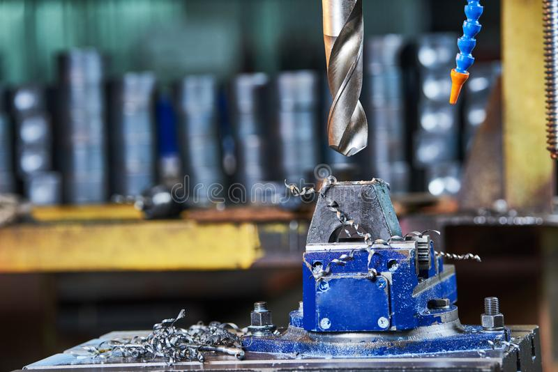 Metalwork drilling the metal detail in factory. Metalwork. Drilling hole in metal detail on drill machine at factory workshop stock image
