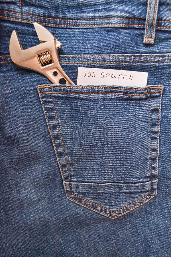 Metalwork keys in jeans pocket, note with the inscription `Job Search`. Symbolizes the onset of the economic crisis royalty free stock images