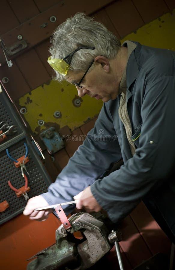 Metalworker em sua oficina imagens de stock royalty free