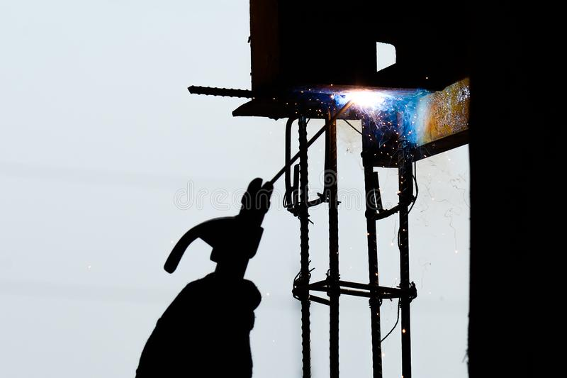 Metalworker at work welding steel with spread spark and lighting around.Hand of Steel Workers welding steel bar construction royalty free stock images