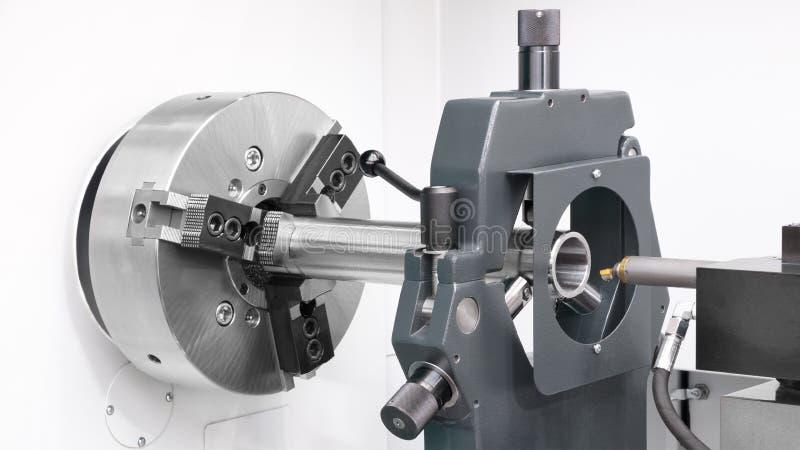 Metalworking cnc-bransch: axel för klippstålmetall som bearbetar på drejbänkmaskinen i seminarium arkivfoto