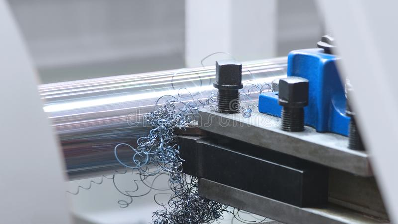 Metalworkingbransch: bitande st?lmetallaxel som bearbetar p? drejb?nkmaskinen i seminarium Selektiv fokus p? hj?lpmedlet arkivfoto
