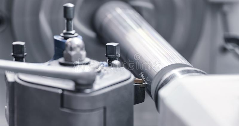 Metalworkingbransch: bitande st?lmetallaxel som bearbetar p? drejb?nkmaskinen i seminarium Selektiv fokus p? hj?lpmedlet arkivbild