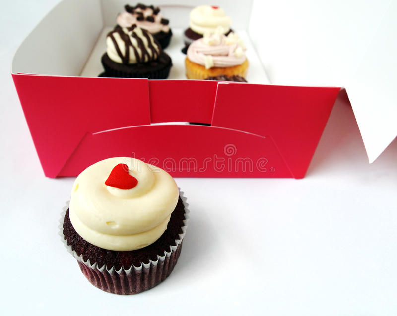 Metaphor - out of the box. A versatile photograph showing some luxury goumet cup cakes sitting pretty in a special cardboard take out carrying box made for half stock photo