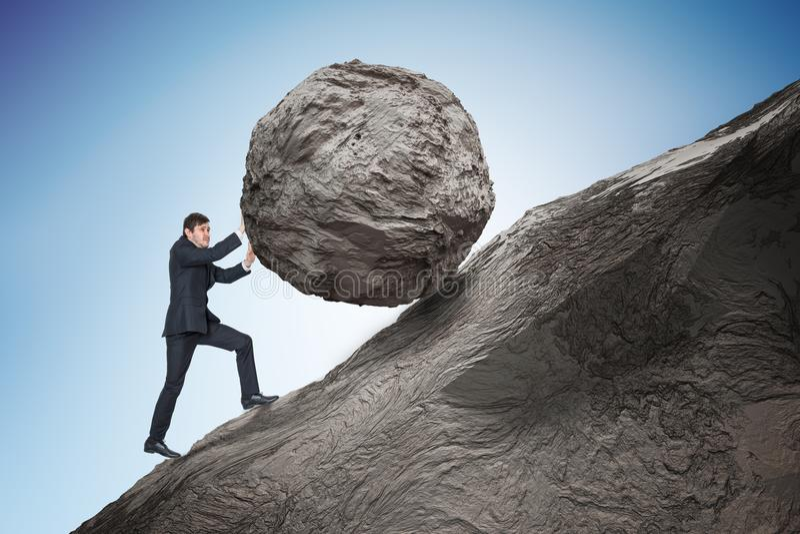 Metaphore de Sisyphus Homem de negócios novo que empurra o pedregulho de pedra pesado acima no monte fotografia de stock