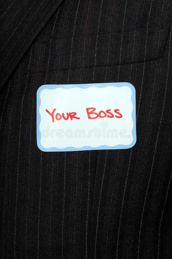 Metaphorical boss. Closeup of a man's chest in a business suit with a nametag that says your boss royalty free stock photo