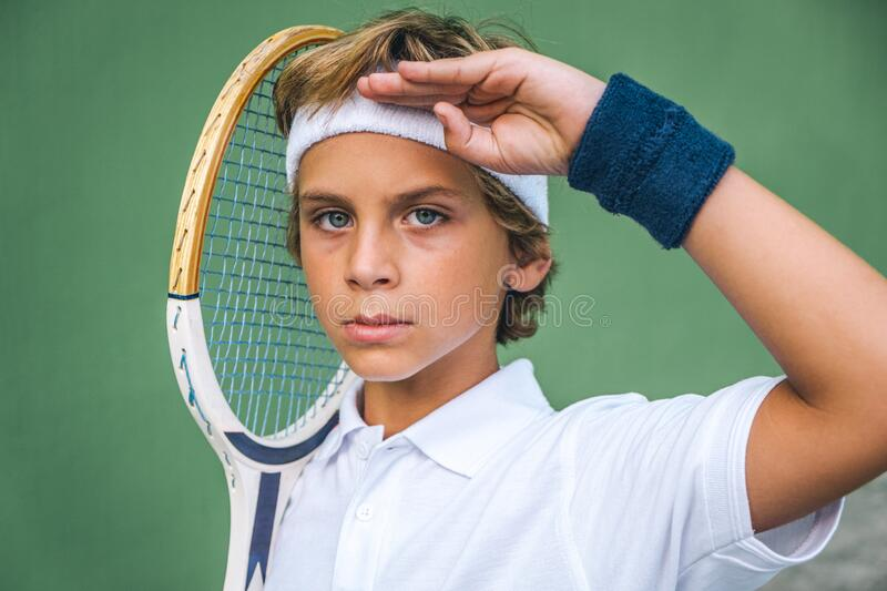 Tennis boy makes the military salute posing with his racket as if it were a rifle royalty free stock photos
