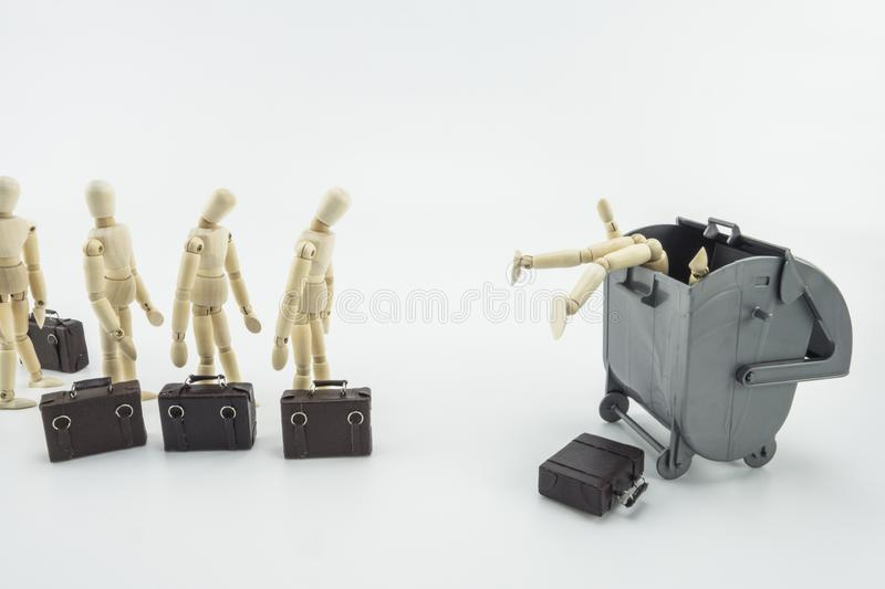 Metaphorical scene, executives throwing to a dustbin, isolated wooden dolls on white background. Horizontal composition stock photo