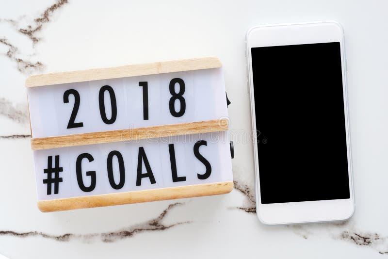 2018 metas en la caja de madera y el teléfono elegante con el espacio en blanco en la pantalla en o fotografía de archivo libre de regalías