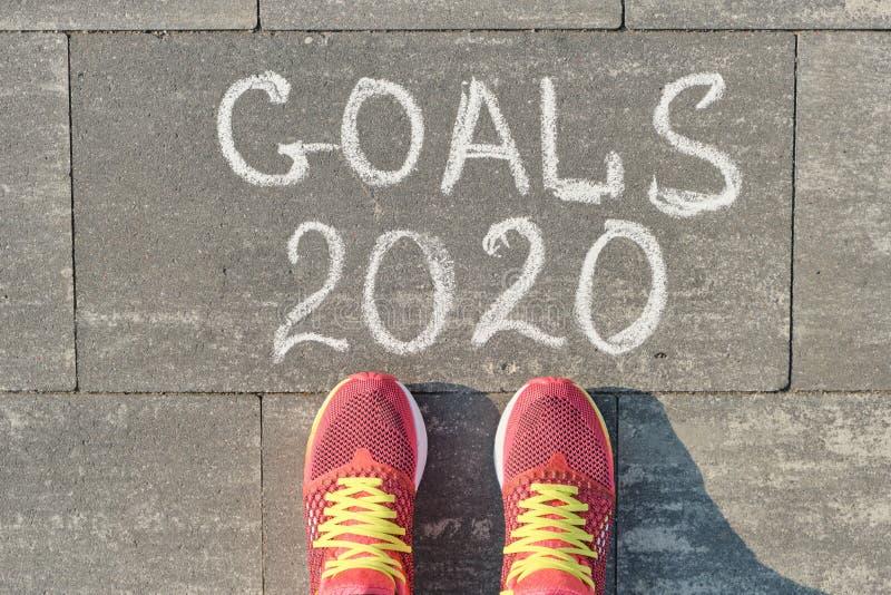 2020 metas, escritas en la acera gris con las piernas de la mujer en zapatillas de deporte, visión superior fotos de archivo