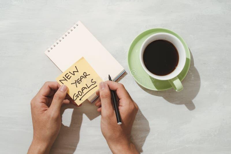 Metas o resoluciones - notas pegajosas amarillas del Año Nuevo con café en la tabla fotos de archivo