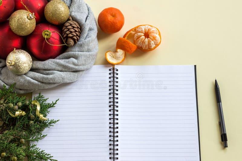 2019 metas Para hacer la lista en libreta al lado de decoraciones, de conos y de mandarinas de la Navidad foto de archivo