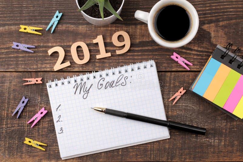 Metas para 2019 texto en cuaderno con la pluma y el café en un fondo de madera marrón Visión desde arriba fotografía de archivo libre de regalías