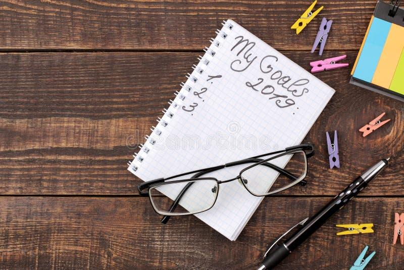 Metas para 2019 texto en cuaderno con la pluma y vidrios en un fondo de madera marrón imagen de archivo libre de regalías