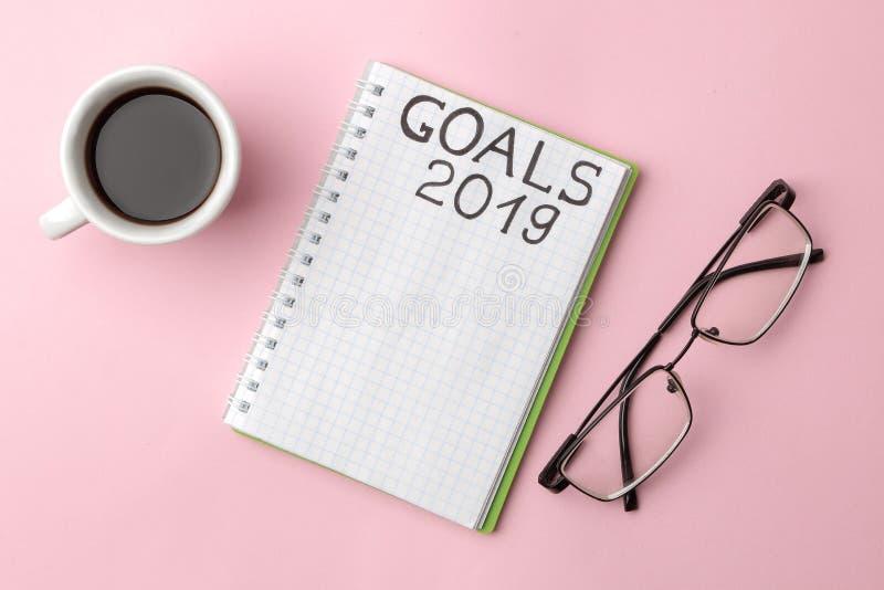 Metas 2019 texto en un cuaderno con vidrios y una taza de café en un fondo rosado brillante fotos de archivo