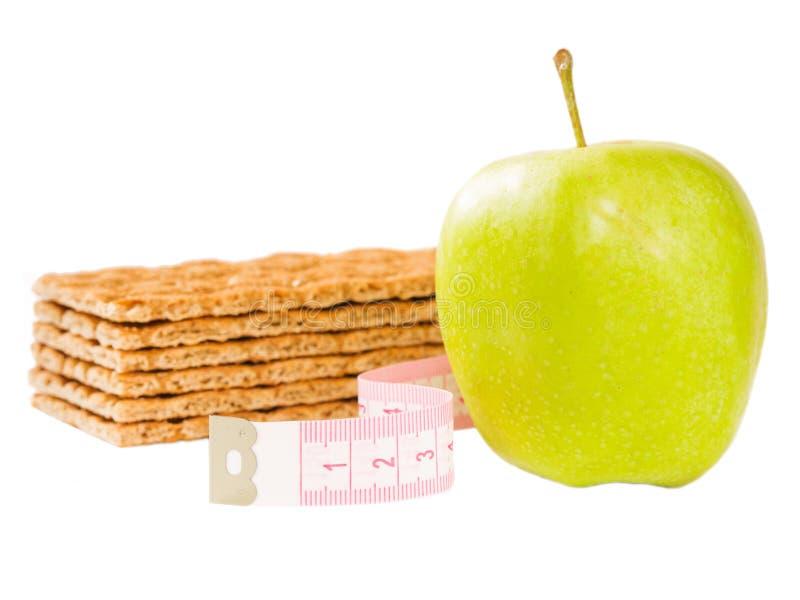 Metend geïsoleerde band, knäckebrood en groene appel stock foto