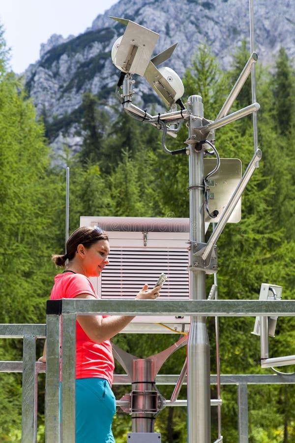 Meteodata ανάγνωσης μετεωρολόγων γυναικών στον καιρικό σταθμό βουνών στοκ εικόνα