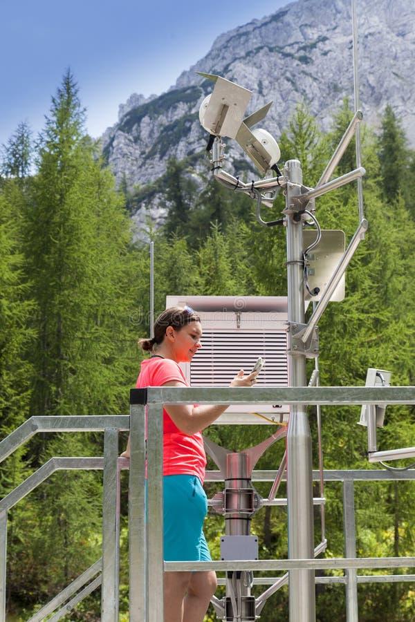 Meteodata ανάγνωσης μετεωρολόγων γυναικών στον καιρικό σταθμό βουνών στοκ φωτογραφία