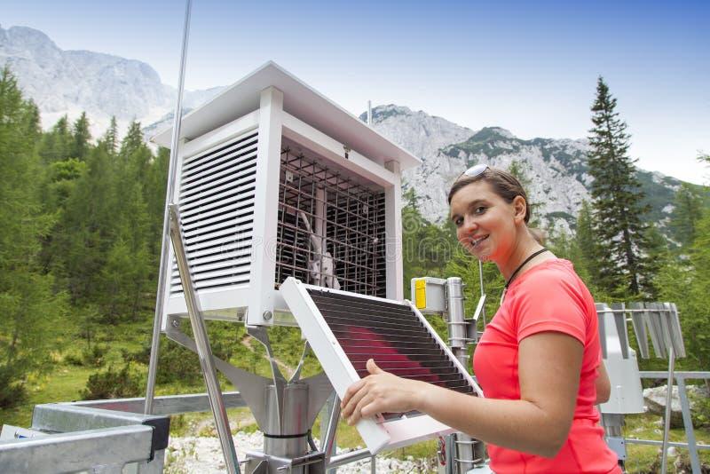 Meteodata da leitura do meteorologista da mulher na estação meteorológica da montanha fotografia de stock