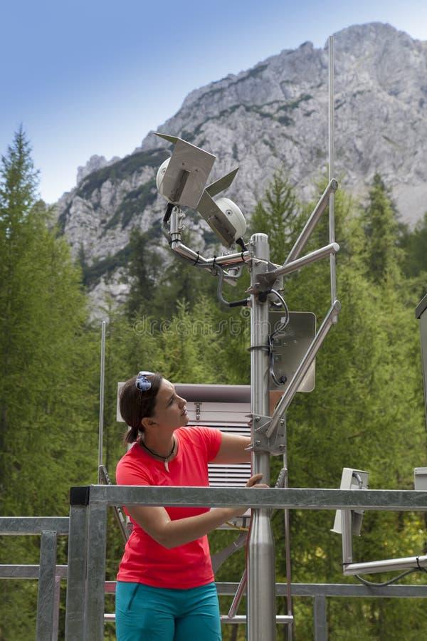 Meteodata de lecture de météorologiste de femme dans la station météorologique de montagne photographie stock libre de droits
