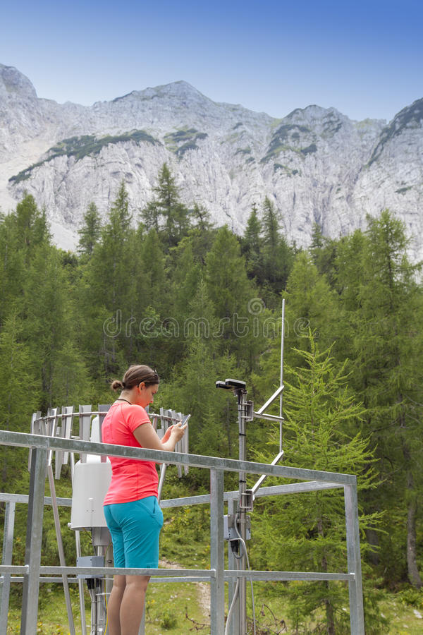 Meteodata de lecture de météorologiste de femme dans la station météorologique de montagne photo libre de droits