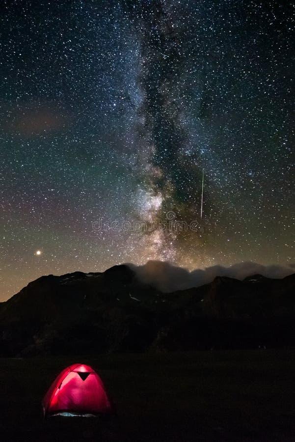 Meteoor met de groene melkachtige manier van de staart sterrige hemel Verlichte tent in de voorgrond, die op de Alpen kamperen De stock afbeelding