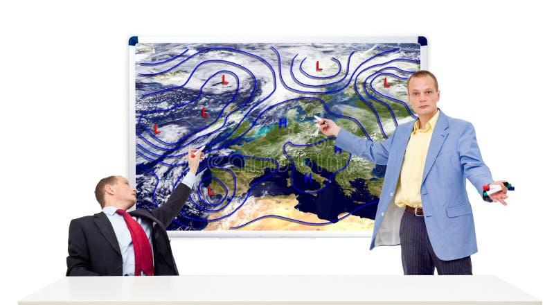 Meteorólogos detrás de un escritorio del ancla foto de archivo libre de regalías