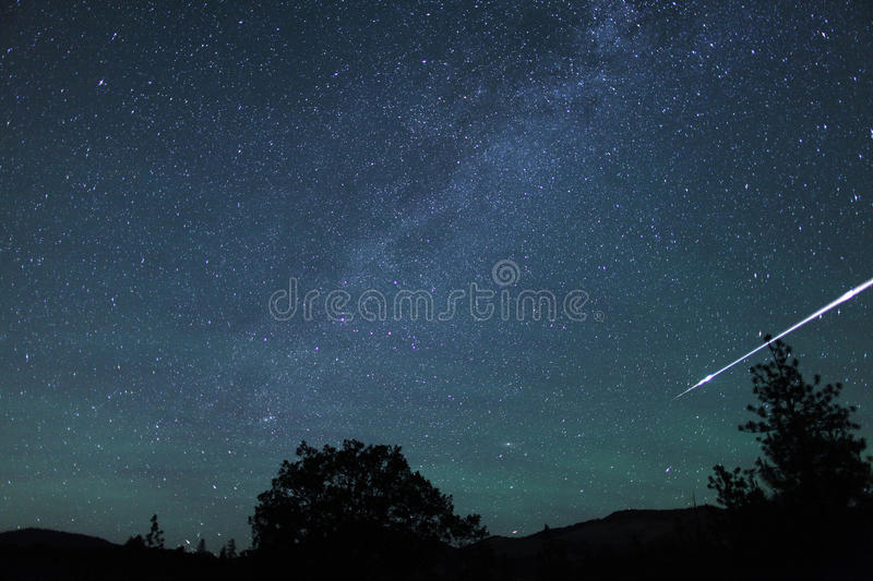 Meteor fireball streaks through the sky. With the Milky Way and Airglow in the night sky, Oregon, Cascade Siskiyou National Monument, Near Ashland, Taken 06/ stock photo