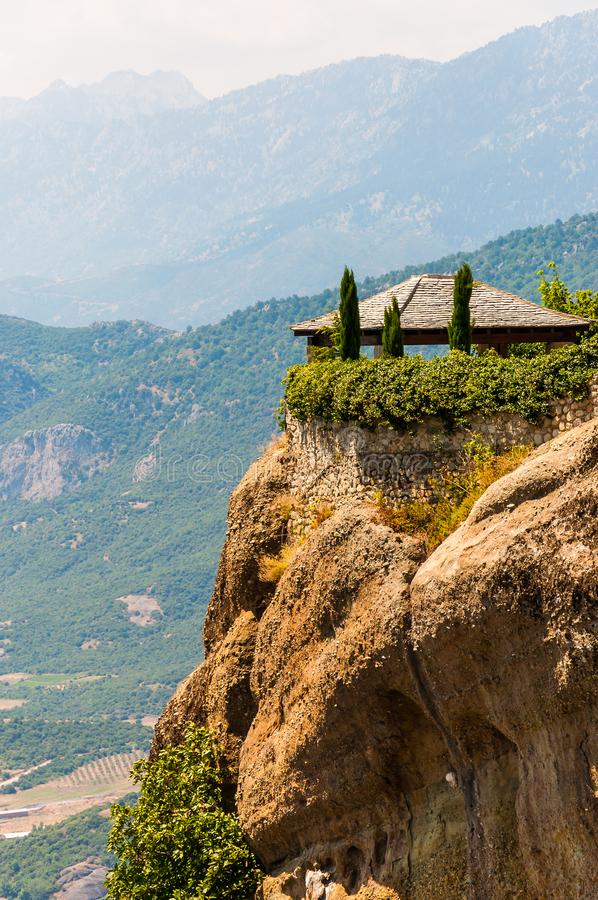 Open garden pavilion of the Saint Stephen Nunnery Monastery on the cliff with amazing scenic view on valleys and mountains range. Meteora, Greece - June 16 stock image