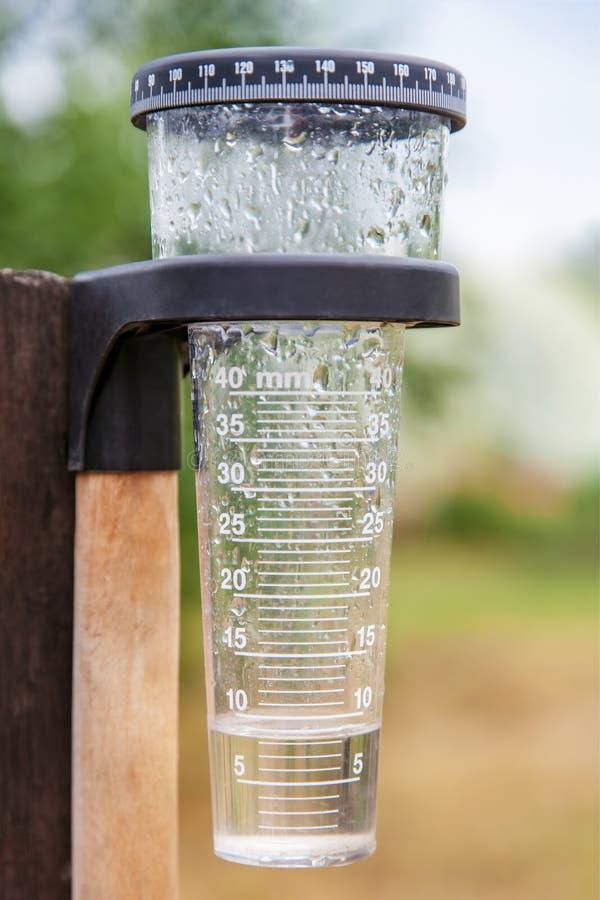 Meteorologia com o calibre de chuva no jardim imagens de stock