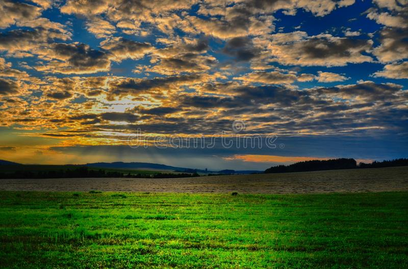 Meteorological photo - clouds over the meadow and agriculture fields at summer sunset. stock photography