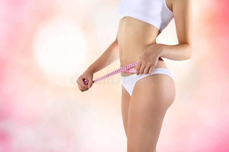 Meter diet on the woman belly pink background royalty free stock photos